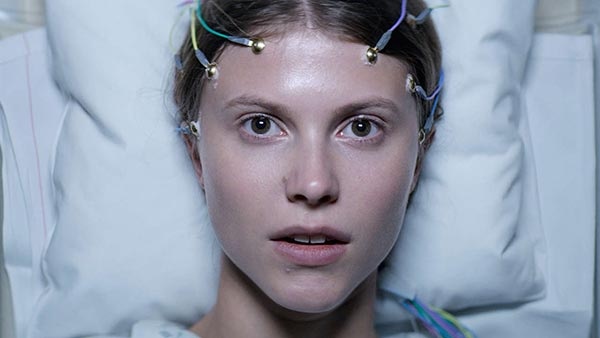 Thelma (2017). A tight close up on Thelma's face as she is lying in a hospital bed with white sheets. She is staring wide eyed at the camera, and has lots of wires with sticky metal pieces on the end attached to her head.